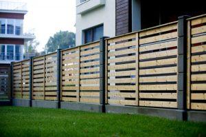 Дерев'яний паркан біля котеджу з бетонних блоків сіточка
